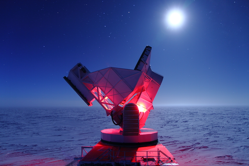 Figure 2: A picture of the South Pole Telescope (SPT) and full moon. This photo shows the SPT observing during the austral winter, with the featureless horizon of the high Antarctic Plateau in the background.